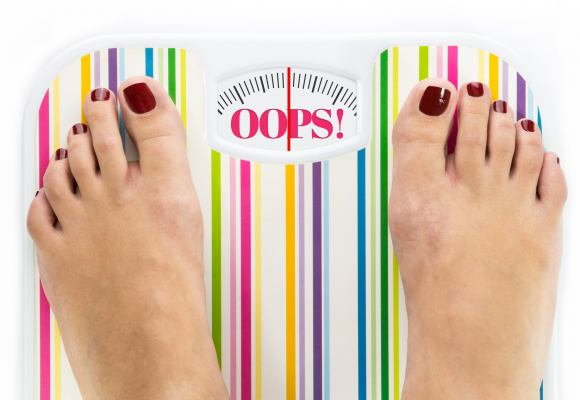 "Feet on bathroom scale with word ""Oops"" on dial"